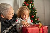 Cheerful senior woman and laughing girl holding christmas gift on sofa. Little girl sitting on grand poster