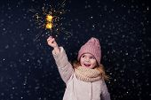 Charming Little Girl In A Knitted Pink Hat Holding Fireworks On Black Background In A Studio.cute Bl poster