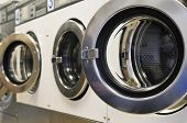 stock photo of oversize load  - A row of industrial washing machines in a public laundromat - JPG
