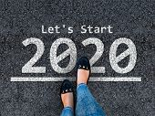 Happy New Year 2020. Lets Start 2020. Woman Legs In Shoes Walks On Asphalt Road Next To Number 2020 poster