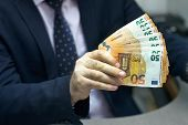 Hand Of Office Worker Gives A Bribe Roll Euro Banknote To An Employee In The Office. Concept - Corru poster