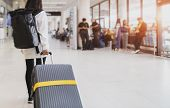 Young Woman Pulling Suitcase In Airport Terminal. Young Woman Traveler In International Airport With poster