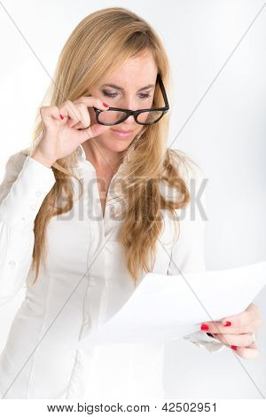 Woman inspecting closely a document through her reading glasses