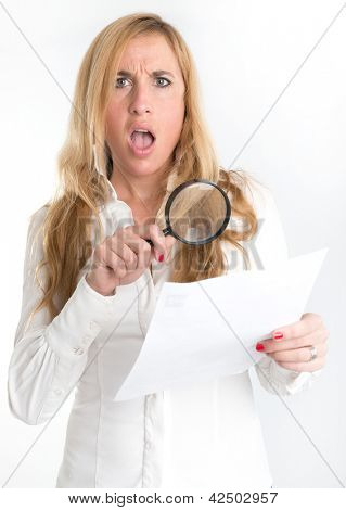 Woman with shocked expression examining a document through a magnifying glass