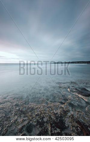 Submerged Rocks, Ocean And Cloudy Sky On Bay Beach