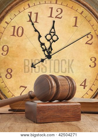 Wooden gavel and old vintage clock