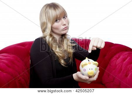 Young Blond Haired Girl Want Money In Her Piggybank On Red Sofa In Front Of White Background