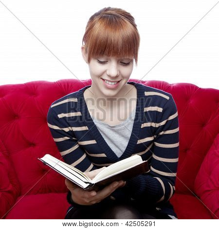 Young Beautiful Red Haired Girl On Red Sofa Read A Book In Front Of White Background