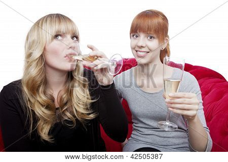 Young Beautiful Blond And Red Haired Girls Drink Champagne And Cheer On Red Sofa In Front Of White B