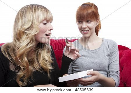 Young Beautiful Blond And Red Haired Girls Eating Chocolate On Red Sofa In Front Of White Background