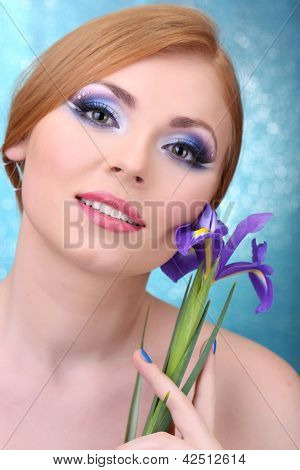 Beautiful young woman with glamour make up and flower on blue background
