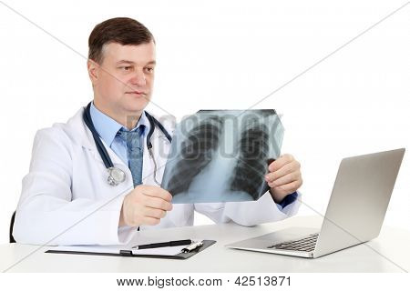 Medical doctor analysing x-ray image at desk isolated on white