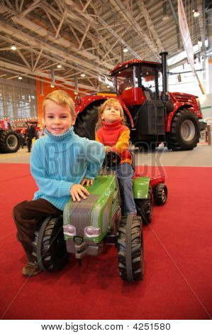 Girl Astride A Small Tractor The Boy Sits Next