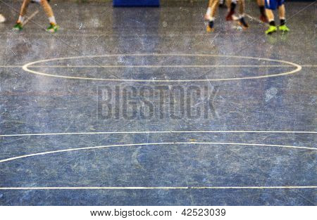 Vintage photo of school gym floor with out of focus legs of children playing basketball in the background