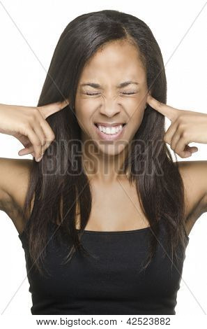 Woman blocking irritating noise by putting fingers in ears.