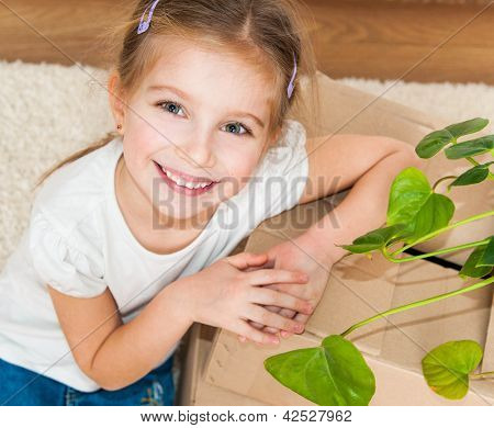 Little girl siting near cardboard box and plant.  top view