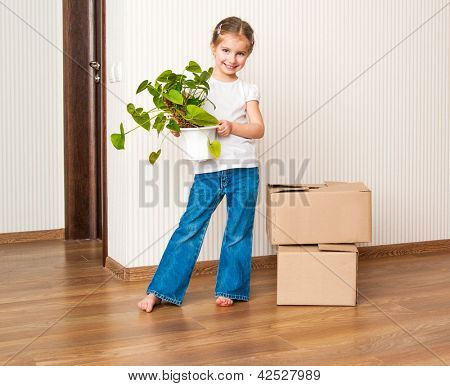 Little girl moving into new house, carrying cardboard box and green plant