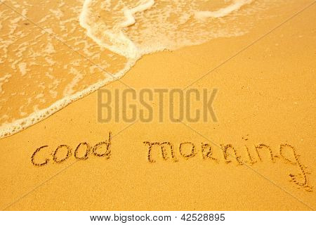 Good morning - written in sand on beach texture - soft wave of the sea