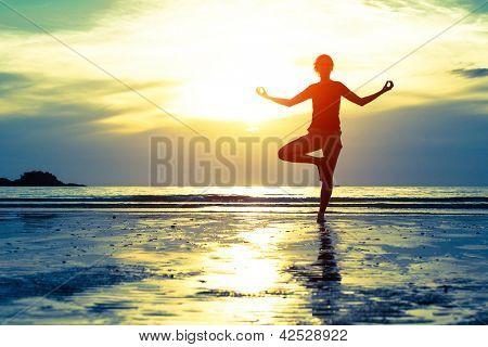 Mujer practicando yoga en la playa al atardecer