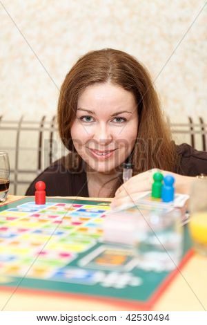 Caucasian Woman Playing Board Games In Domestic Room