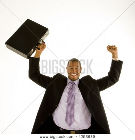 Black Man In Suit Raising Fist And Briefcase Over Head