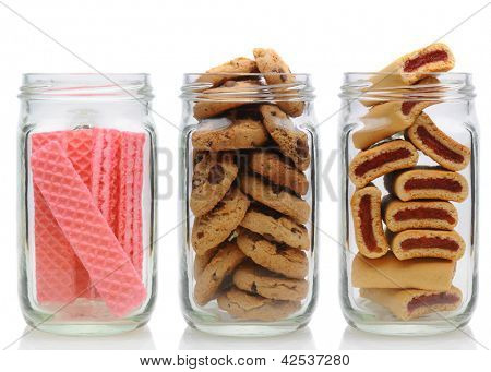 Three glass jars filled with cookies, on a white background with reflection. Jars contain, pink sugar wafers, chocolate chip and fruit bars.