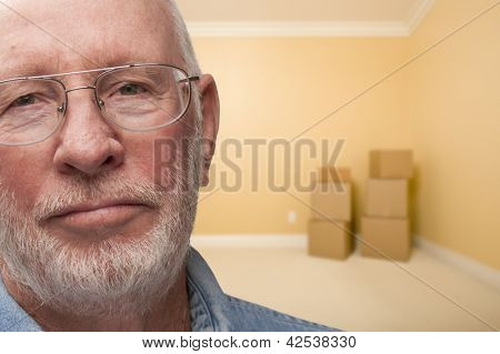 Sad Older Man In Empty Room with Boxes - Concept for Foreclosure, Divorce, Moving, etc.