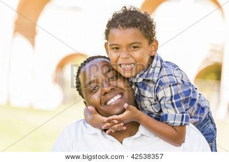 Happy Mixed Race Father and Son Playing Piggyback in the Park.