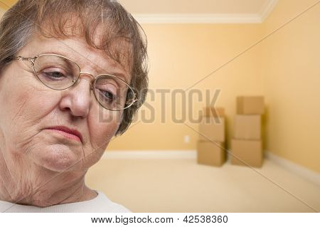 Sad Older Woman In Empty Room with Boxes - Concept for Foreclosure, Divorce, Moving, etc.