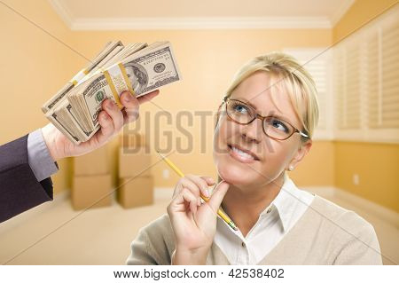 Woman Holding Pencil Being Handed Stack of Money in Empty Room with Boxes.