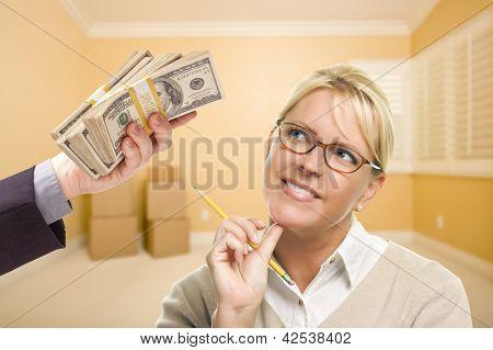 Постер, плакат: Женщина держащая карандаш передачи стек денег в пустой комнате с коробки , холст на подрамнике