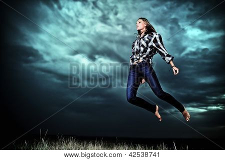 Beautiful young woman jumping in the field over stormy evening sky.