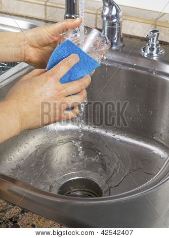 Female Hands Running Water Into Soapy Drinking Glass