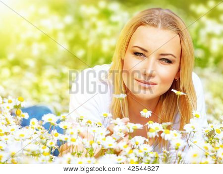 Picture of beautiful female lying down on chamomile meadow in sunny day, attractive young lady resting on white flowers field, rural place, relaxation outside, spring holiday and vacation concept