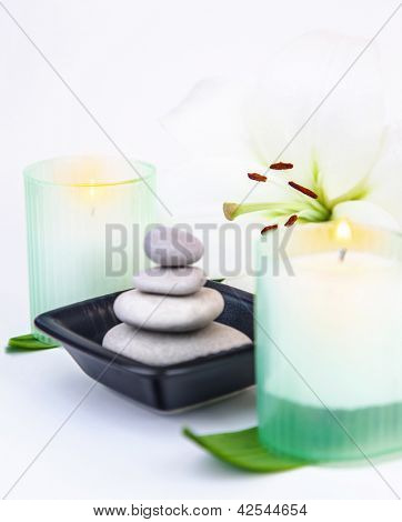 Image of pebble stones in black bowl, aroma candle, fresh green leaves, lily flower isolated on white background, enjoying day spa, aromatic massage, essential oil, zen balance, stress treatment