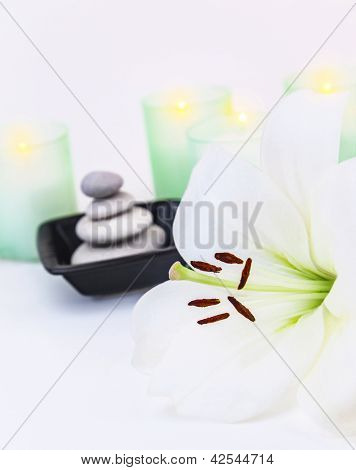 Image of beautiful white lily flower, pebble stones, two candles, spa still life, dayspa, luxury beauty salon, hygiene items, bath objects, healthy lifestyle, organic cosmetics, vacation concept