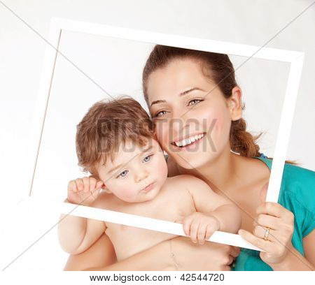 Image of nice mother with lovely son hugging and isolated on white background, beautiful woman with cute toddler holding in hands white frame, happy childhood, love concept