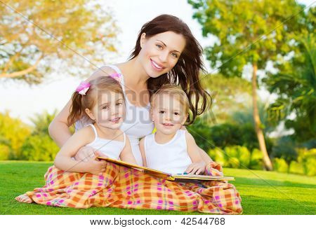 Photo of attractive brunette woman with two little smart children sitting down on green field in park in spring time and read book, mother with daughter and son enjoy fairytale, happy family concept
