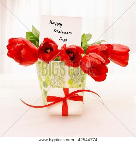 Picture of fresh red tulip flowers in beautiful vase with paper greeting postcard on the table, little white gift box with ribbon, home interior, happy mothers day, festive still life, love concept