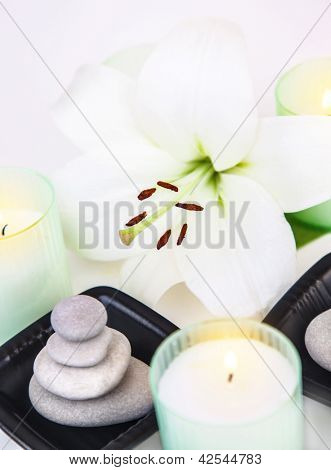 Picture of white lily flower, pebble stones, aromatic candles, closeup of spa still life, spa salon decorations, peace and meditation, herbal massage, zen balance, enjoying dayspa