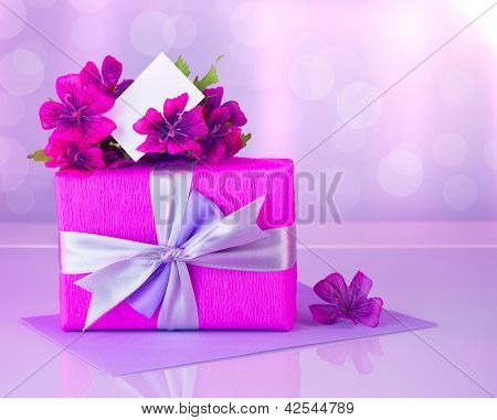 Picture of pink gift box with purple silk ribbon, beautiful violet wild flowers bouquet, white blank greeting card, beautiful romantic still life, blur background, happy mothers day, reflection