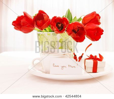 Photo of fresh red tulip flowers in beautiful vase on table, cup of tea, little white gift box with ribbon, festive postcard with ladybird decorations, home interior, happy mothers day, love concept
