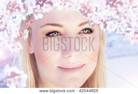 Picture of beautiful woman outdoors in spring time, closeup portrait of cute blonde female wearing pink floral wreath, cherry blossom, spring flowers blooming, natural makeup, harmony concept