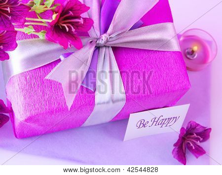 Picture of big pink present box, candle and purple flowers on the table at home, paper greeting card, happy mothers day, romantic holiday, gift for birthday, wedding day, romance and love concept