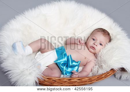 Portrait Of Newborn Baby Lying On Fur With Blue Bow In Bed