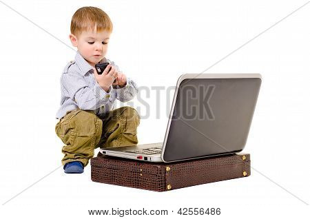 Cute little boy dials on a mobile phone while sitting next to laptop