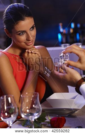 Beautiful young woman sitting at dinner table, man handing over engagement ring. Only woman can be seen.