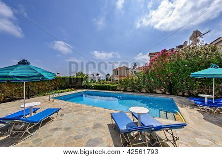 Umbrellas And Sunbeds Near The Pool