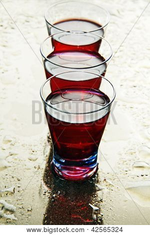 Glasses Of Wine On A Wet Mirror.