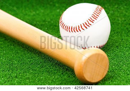 Close-up of baseball ball and bat on artificial green grass
